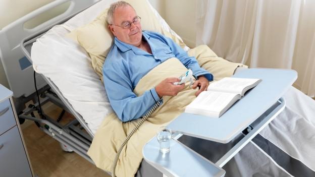 Homme lisant a l'aide d'une table de lit